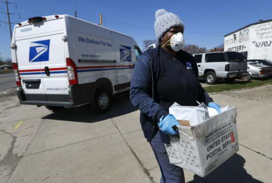 FILE - In this April 2, 2020 file photo, a United States Postal  Service worker makes a delivery with gloves and a mask in Warren, Mich. A group of states suing over service cuts at the U.S. Postal Service is asking a federal judge to immediately undo some of them, saying the integrity of the upcoming election is at stake.(AP Photo/Paul Sancya,File)
