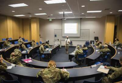 In this image provided by the U.S. Air force Academy, academy cadetsstart the school year with a mix of reduced class sizes and remote learning on Aug. 12, 2020, at the U.S. Air Force Academy in Colorado Springs, Colo. Under the siege of the coronavirus pandemic, classes have begun at the Naval Academy, the Air Force Academy and the U.S. Military Academy at West Point. But unlike at many colleges around the country, most students are on campus and many will attend classes in person. (Trevor Cokley/U.S. Air Force Academy via AP)