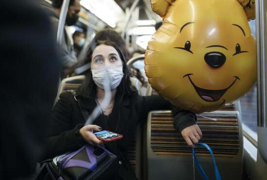 A masked woman holds a Winnie the Pooh inflatable balloon, inside the subway, in Paris, Thursday Oct.29, 2020. Some doctors expressed relief but business owners despaired as France prepared to shut down again for a month to try to put the brakes on the fast-moving virus. (AP Photo/Lewis Joly)