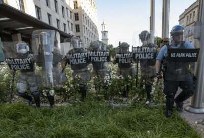 FILE - In this June 1, 2020, file photo, District of Columbia National Guard, and U.S. Park Police, advance through the white roses in front of the AFL-CIO headquarters, with St. John's Church behind them, as they move demonstrators back after they gathered to protest the death of George Floyd near the White House in Washington. The National Guard has designated military police units in two states to serve as rapid reaction forces in order to be better prepared to respond quickly to civil unrest around the country, in the wake of the violent protests that rocked the nation's capitol and several states this summer.  (AP Photo/Alex Brandon, File)