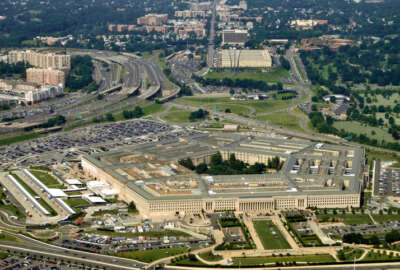 Aerial of the Pentagon, the Department of Defense headquarters in Arlington, Virginia, near Washington DC, with I-395 freeway on the left, and the Air Force Memorial up middle.