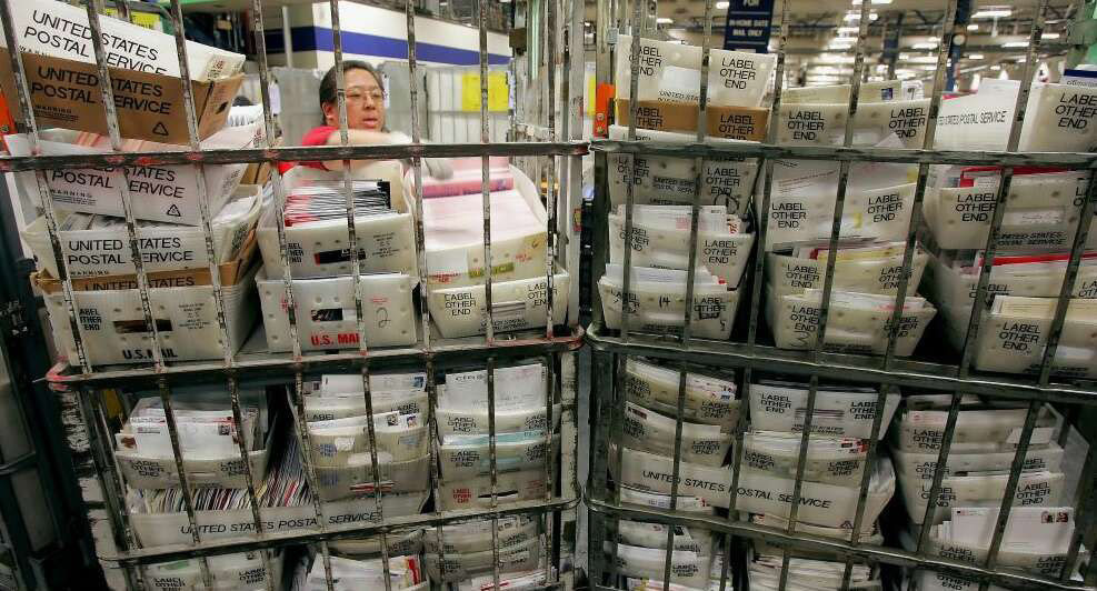 A worker sorts mail at a USPS Mailroom