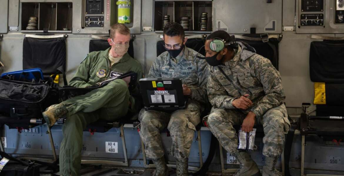 Maj. Philip Becker, 8th Airlift Squadron pilot, left, works with 62nd Aircraft Maintenance Squadron Airmen to complete preflight checks at Joint Base Lewis-McChord, Wash., Aug. 6, 2020. The flight was part of Exercise Long Hammer/Rainier War, a week-long exercise designed to evaluate Team McChord's ability to conduct airlift operations while complying with real-world COVID-19 pandemic countermeasures. (U.S. Air Force photo by Senior Airman Sara Hoerichs)