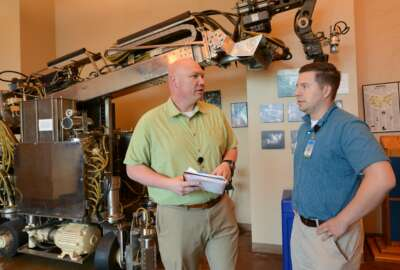Doug Matty (left), director of AI capabilities at the Army's AI Task Force, discusses an AI app for talent management being developed by Maj. Kevin Goulding (right). Behind them in the lobby of the National Robotics Engineering Center .