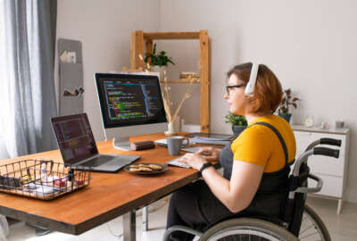 Smart disabled coder sitting in wheelchair and using computers while working from home