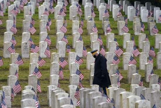 Retired U.S.Army veteran Bill MacCully walks among flag-covered graves in the Veterans Cemetery of Evergreen Washelli Memorial Park on Veterans Day, Wednesday, Nov. 11, 2020, in Seattle. (AP Photo/Elaine Thompson)