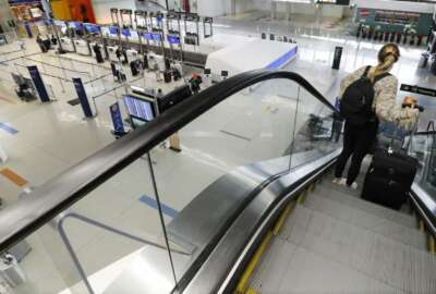 A traveler rides an escalator with her luggage as she arrives at the nearly empty JetBlue terminal at Logan Airport, Friday Nov. 20, 2020, in Boston. With the coronavirus surging out of control, the nation's top public health agency pleaded with Americans not to travel for Thanksgiving and not to spend the holiday with people from outside their household. (AP Photo/Michael Dwyer)