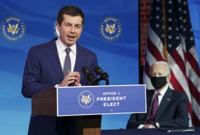 Former South Bend, Ind. Mayor Pete Buttigieg, President-elect Joe Biden's nominee to be transportation secretary reacts to his nomination as Biden looks on during a news conference at The Queen theater in Wilmington, Del., Wednesday, Dec. 16, 2020. (Kevin Lamarque/Pool via AP)