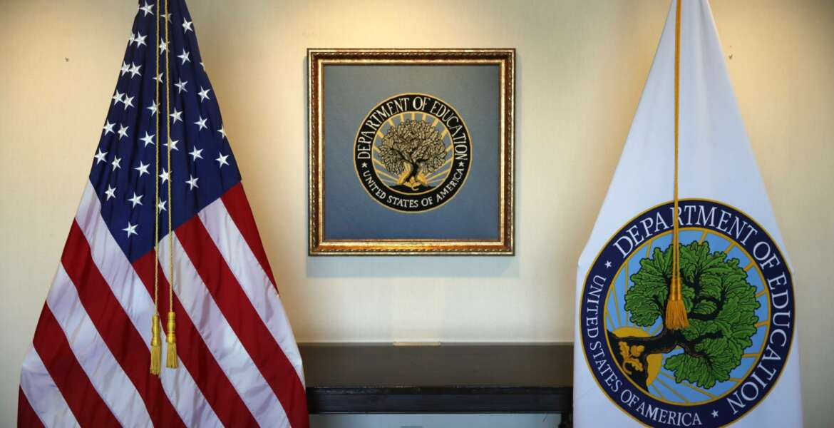 FILE - In this Aug. 9, 2017, photo, flags decorate a space outside the office of the Education Secretary at the Education Department in Washington. President-elect Joe Biden has chosen the education commissioner for Connecticut and a former public school teacher to serve as education secretary. (AP Photo/Jacquelyn Martin)