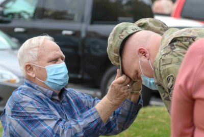 Retired Sgt. 1st Class Eugene Patton Sr. affixes the insignia on his son 1st Sgt. Eugene Patton Jr. patrol cap during a promotion ceremony on October 20, 2020. (Photo by Staff Sgt. Zach Sheely)