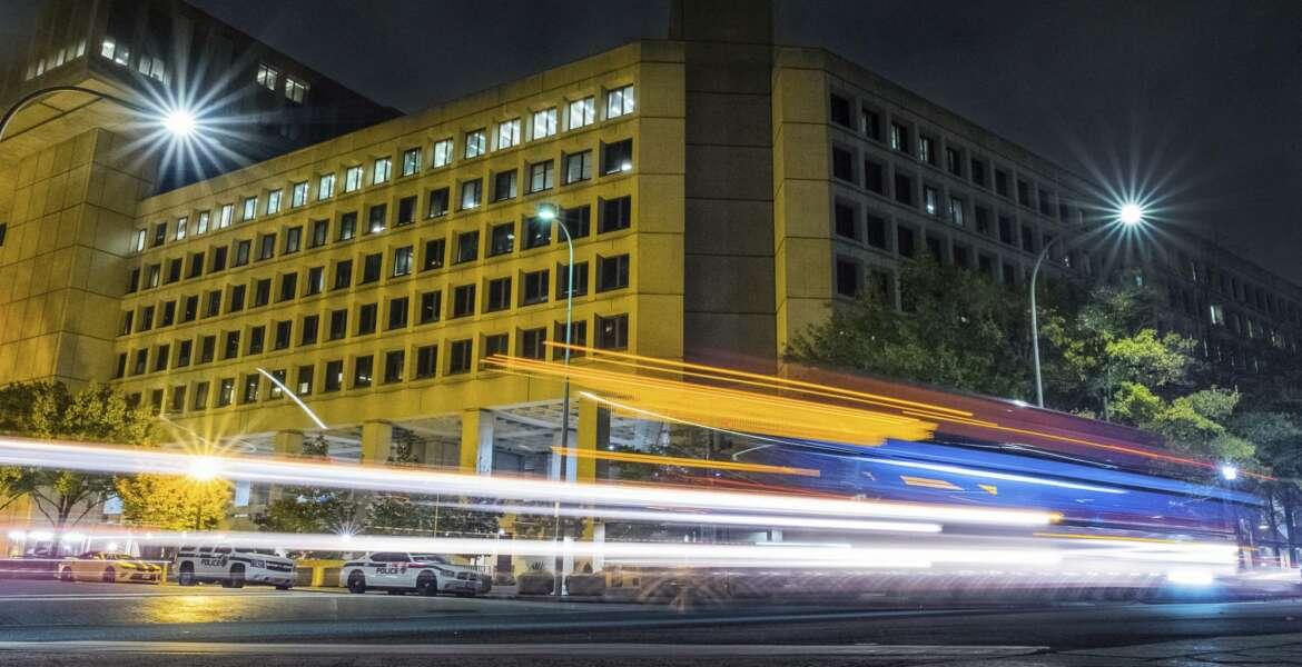 FILE - In this Nov. 1, 2017, file photo, traffic along Pennsylvania Avenue in Washington streaks past the Federal Bureau of Investigation headquarters building. The FBI has been shaken by a series of sexual misconduct cases involving senior leadership over the past few years, including two new claims brought in December 2020 by women who say they were sexually assaulted by supervisors. (AP Photo/J. David Ake, File)