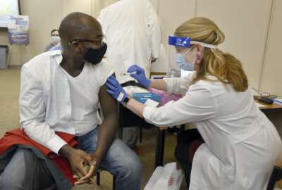 Dr. Cletus Oppong, who specializes in occupational medicine, is the first to receive the first round of the Moderna vaccine by Clinical Pharmacist Erin Conkright on Thursday morning , Dec. 24, 2020, at the Owensboro Health Regional Hospital in Owensboro, Ky.
