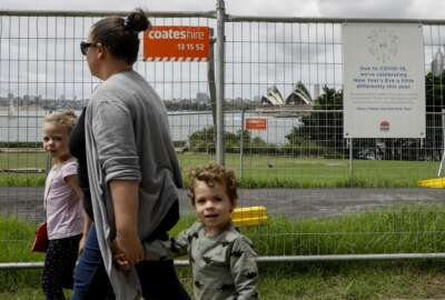 A family walks past a fence near the harbour foreshore ahead of New Years Eve in Sydney, Australia, Thursday, Dec. 31, 2020. One million people would usually crowd the Sydney Harbor to watch the annual fireworks that center on the Sydney Harbor Bridge. But this year authorities are advising revelers to watch the fireworks on television (AP Photo/Mark Baker)