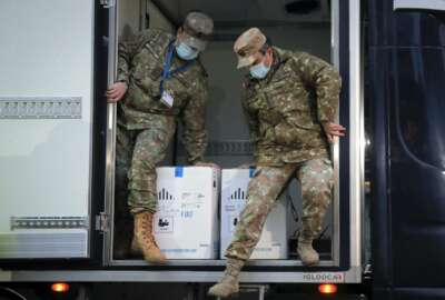 Romanian servicemen, wearing masks to protect against coronavirus, prepare to unload boxes containing the first batch of COVID-19 vaccines, at the National Center for Storage of the COVID-19 Vaccine, a military run facility, in Bucharest, Romania, Saturday, Dec. 26, 2020. Romanian authorities will start COVID-19 vaccinations on Sunday. (AP Photo/Vadim Ghirda)