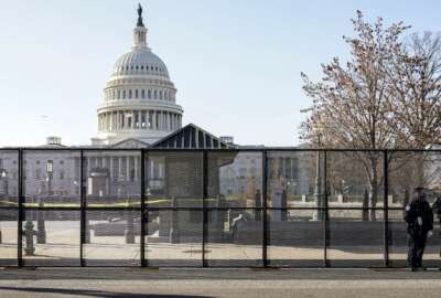 Capitol police officers stand outside of fencing that was installed around the exterior of the Capitol grounds, Thursday, Jan. 7, 2021 in Washington. The House and Senate certified the Democrat's electoral college win early Thursday after a violent throng of pro-Trump rioters spent hours Wednesday running rampant through the Capitol. A woman was fatally shot, windows were bashed and the mob forced shaken lawmakers and aides to flee the building, shielded by Capitol Police. (AP Photo/John Minchillo)