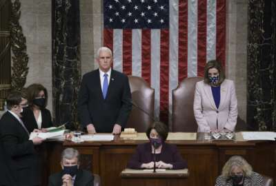 Vice President Mike Pence and Speaker of the House Nancy Pelosi, D-Calif., read the final certification of Electoral College votes cast in November's presidential election during a joint session of Congress after working through the night, at the Capitol in Washington, Thursday, Jan. 7, 2021. Violent protesters loyal to President Donald Trump stormed the Capitol Wednesday, disrupting the process. (AP Photo/J. Scott Applewhite, Pool)
