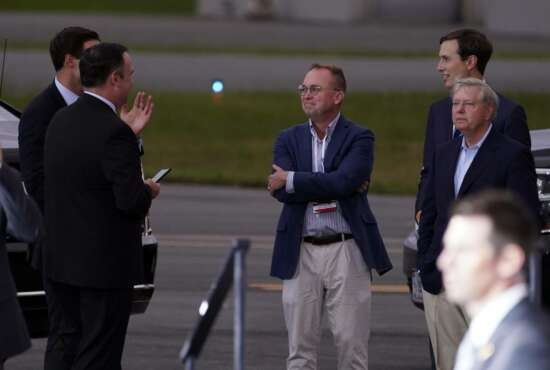 White House social media director Dan Scavino, from left, White House aide John McEntee former acting chief of staff Mick Mulvaney, White House adviser Jared Kushner and Sen. Lindsey Graham, R-S.C., talk as President Donald Trump speaks during a campaign rally at Smith Reynolds Airport, Tuesday, Sept. 8, 2020, in Winston-Salem, N.C. (AP Photo/Evan Vucci)