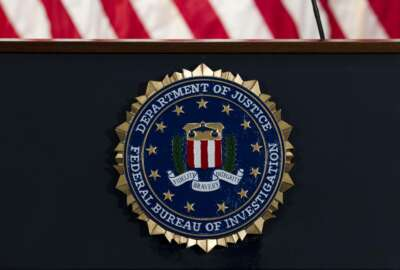 FILE - In this June 14, 2018, file photo, the FBI seal is seen before a news conference at FBI headquarters in Washington. A former FBI lawyer was sentenced to probation for altering a document the Justice Department relied on during its surveillance of a Donald Trump aide during the Russia investigation. (AP Photo/Jose Luis Magana, File)