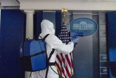 FILE - In this Oct. 5, 2020, file photo, a member of the cleaning staff sprays The James Brady Briefing Room of the White House, Monday, Oct. 5, 2020, in Washington. The U.S. death toll from the coronavirus has eclipsed 400,000 in the waning hours in office for President Donald Trump. (AP Photo/Alex Brandon, File)