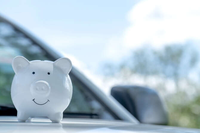 White piggy bank on the car, Money-saving concept for insurance, or traveling during retirement.