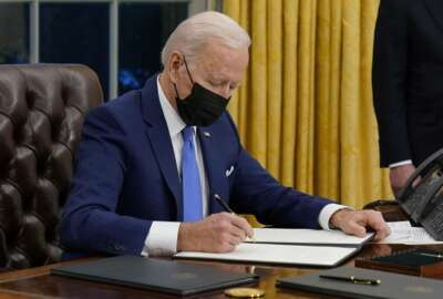 President Joe Biden signs an executive order on immigration, in the Oval Office of the White House, Tuesday, Feb. 2, 2021, in Washington. (AP Photo/Evan Vucci)