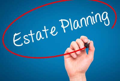Man Hand writing Estate Planning with black marker on visual screen. Isolated on blue. Business, technology, internet concept. Stock Photo