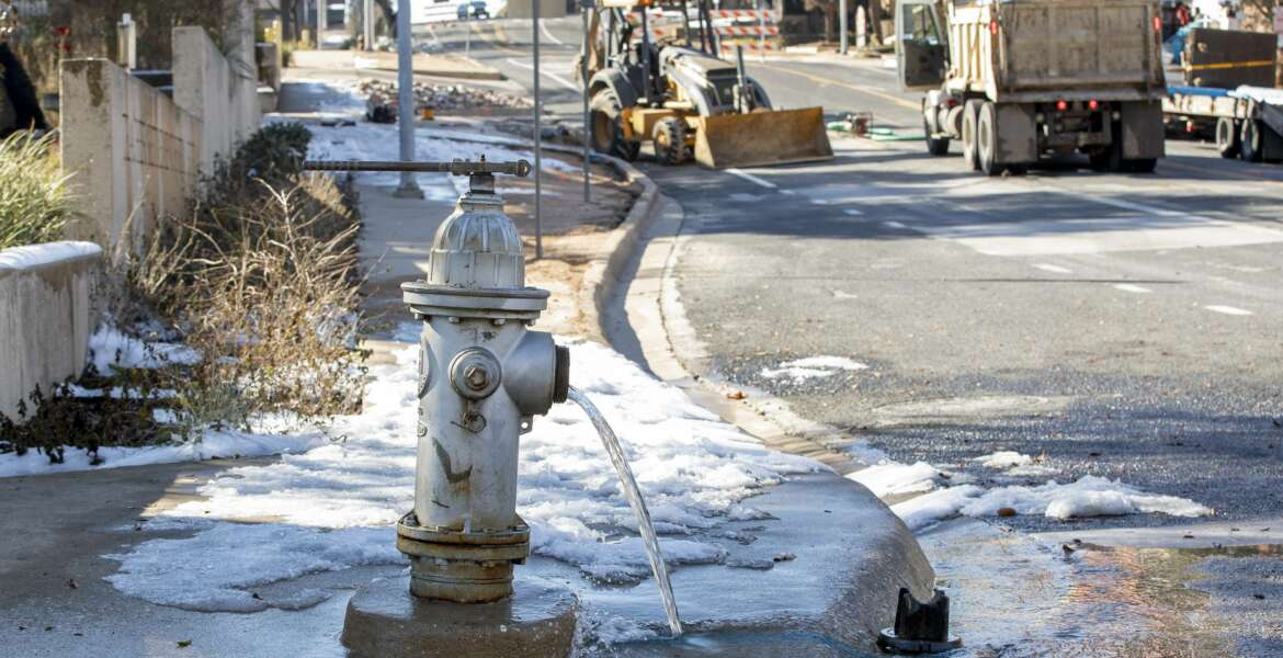 FILE - In this Feb. 21, 2021 file photo, water trickles from a fire hydrant while City of Austin Water Utility workers repair a broken water main in Austin, Texas, due to severe winter weather. The winter storm nightmare knocked out power to more than 4 million customers across the state. On Thursday, Feb. 25 managers of Texas' power grid are expected to receive a verbal lashing in the first public hearings about the crisis at the state Capitol. (Jay Janner/Austin American-Statesman via AP, File)