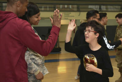 """U.S. Airmen and the child of a DoD service member congratulate each other after a """"Vogelweh Gym Session"""" at Vogelweh Military Complex, Germany, Oct. 9, 2019. Active duty service members are invited to sign up and play with special needs children on the second Wednesday of each month during the school year. (U.S. Air Force photo by Senior Airman Elizabeth Baker)"""