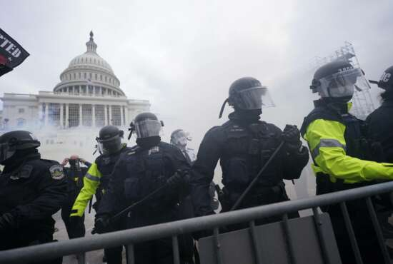 FILE - In this Jan. 6, 2021, file photo, police stand guard after holding off rioters who tried to break through a police barrier at the Capitol in Washington. Hundreds of emails, texts, photos and documents obtained by the Associated Press show how a patchwork of law enforcement agencies from all directions tried to give support as protesters poured into town. But a lack of coordination and adequate planning left the Capitol vulnerable, and resulted in a deadly_and potentially avoidable_breach.(AP Photo/Julio Cortez, File)