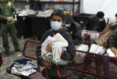 A young migrant waits for his turn to take a shower at the Donna Department of Homeland Security holding facility, the main detention center for unaccompanied children in the Rio Grande Valley, in Donna, Texas, Tuesday, March 30, 2021. (AP Photo/Dario Lopez-Mills, Pool)