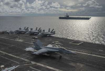 In this photo provided by U.S. Navy, an F/A-18E Super Hornet lands on the flight deck of the USS Ronald Reagan (CVN 76), as USS Nimitz (CVN 68) steams alongside in the South China Sea, Monday, July 6, 2020. Activity by the U.S. Navy in its campaign to challenge China's efforts to restrict transit in the South China Sea and in the Taiwan Strait increased sharply over the past two years.  (Mass Communication Specialist 2nd Class Samantha Jetzer/U.S. Navy via AP)