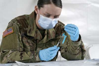 FILE - U.S. Army medic Kristen Rogers of Waxhaw, N.C. fills syringes with the Johnson & Johnson COVID-19 vaccine, Wednesday, March 3, 2021, in North Miami, Fla.  Critics in Florida say a doctor's signature required for some people to get vaccinated is adding onerous barriers for some eligible residents, especially low-income or minority people who may not have health insurance or access to a primary care doctor.  (AP Photo/Marta Lavandier)