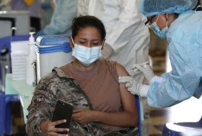 An Air Force member takes a selfie while getting her shot of the Pfizer vaccine for COVID-19 at a military base in Lima, Peru, Monday, March 8, 2021. (AP Photo/Martin Mejia)