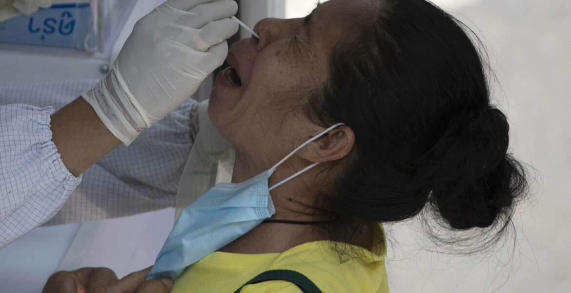 A health worker collects a nasal swab from a woman for a coronavirus test in Bangkok, Thailand, Monday, March 15, 2021. Thai authorities set up mobile testing units for COVID-19 near a market where a new cluster of over a hundred cases was confirmed over the weekend. (AP Photo/Sakchai Lalit)