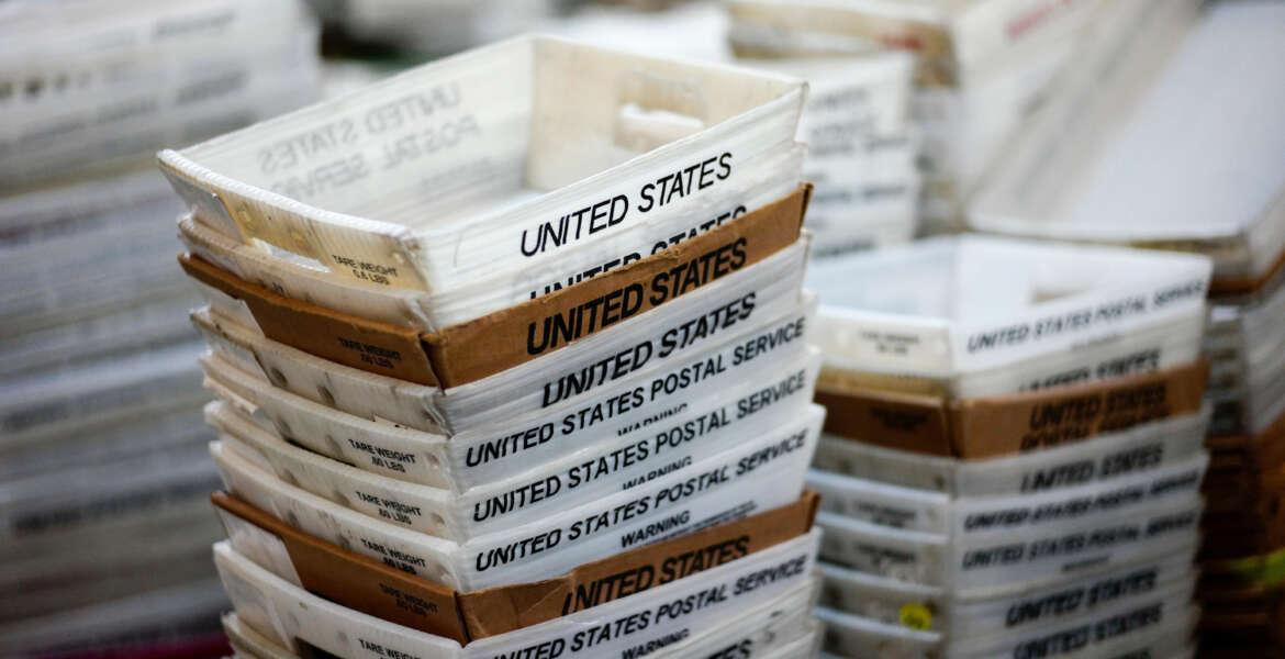 "FILE- In this Dec. 14, 2017, file photo, boxes for sorted mail are stacked at the main post office in Omaha, Neb. A task force created by President Donald Trump to evaluate ways to stem billions of dollars in losses at the U.S. Postal Service is suggesting a range of options, including proposals that could significantly boost the cost of sending non-essential mail. The report recommended that the Postal Service develop a new pricing model that would remove current price caps and charge market-based prices for both mail and packages that were not deemed to be ""essential postal services."". (AP Photo/Nati Harnik, File)"