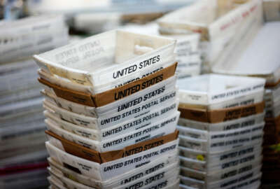 """FILE- In this Dec. 14, 2017, file photo, boxes for sorted mail are stacked at the main post office in Omaha, Neb. A task force created by President Donald Trump to evaluate ways to stem billions of dollars in losses at the U.S. Postal Service is suggesting a range of options, including proposals that could significantly boost the cost of sending non-essential mail. The report recommended that the Postal Service develop a new pricing model that would remove current price caps and charge market-based prices for both mail and packages that were not deemed to be """"essential postal services."""". (AP Photo/Nati Harnik, File)"""