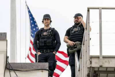 U.S. Secret Service police officers stand guard on the roof in front of the the American flag as it files at half-staff above the White House in Washington, Friday, April 16, 2021. (AP Photo/Andrew Harnik)