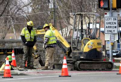 Construction workers work in Wheeling, Ill., Wednesday, March 31, 2021. President Joe Biden will unveil his $2 trillion infrastructure plan and the plan aims to revitalize U.S. transportation infrastructure, water systems, broadband and manufacturing, among other goals. (AP Photo/Nam Y. Huh)