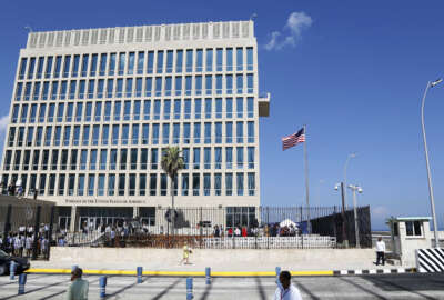"""FILE - In this Aug. 14, 2015, file photo, a U.S. flag flies at the U.S. embassy in Havana, Cuba. The United States is renewing calls for the Cuban government to determine the source of """"attacks"""" on U.S. diplomats in Cuba that have affected some two dozen people. At a senior-level meeting with Cuban officials in Washington on June 14, 2018, the State Department said it had again raised the issue, which has prompted a significant reduction in staffing at the U.S. Embassy in Havana.(AP Photo/Desmond Boylan, File)"""