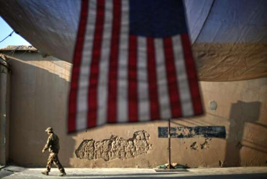 "FILE - In this Sept. 11, 2011 file photo, a U.S. Army soldier walks past an American Flag hanging in preparation for a ceremony commemorating the tenth anniversary of the 9/11 attacks, at Forward Operating Base Bostick in Kunar province, Afghanistan. The final phase of ending America's ""forever war"" in Afghanistan after 20 years formally began Saturday, May 1, 2021, with the withdrawal of the last U.S. and NATO troops by the end of summer.(AP Photo/David Goldman, File)"