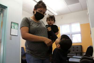 This May 17, 2021 image shows Charrae Toledo dropping off her daughters for the day at Cuidando Los Ninos in Albuquerque, N.M. The charity provides housing, child care and financial counseling for mothers, all of whom will benefit from expanded Child Tax Credit payments that will start flowing in July to roughly 39 million households. (AP Photo/Susan Montoya Bryan)