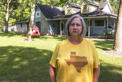 Laurie Fields, who lives in Forest Manor subdivision, speaks during an interview outside her Huffman, Texas home on May 10, 2021. Fields says her home took on feet of water during Hurricane Harvey in 2017 and Tropical Storm Imelda in 2019.  She supports a proposed $1.7 million storm water mitigation project which could help protect her neighborhood from future flooding. (AP Photo/John L. Mone)