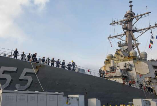 In this photo provided by the U.S. Navy, sailors aboard the guided missile destroyer USS Stout handle mooring lines during the ship's return to home port at Naval Station Norfolk, in Norfolk, Va., in this Oct. 12, 2020, photo. The USS Stout showed rust as it returned from the 210-day deployment. The rust was quickly removed and the ship repainted. But the rusty ship and its weary crew underscored the costly toll of deferred maintenance on ships and long deployments on sailors. (Spc. Jason Pastrick/U.S. Navy via AP)