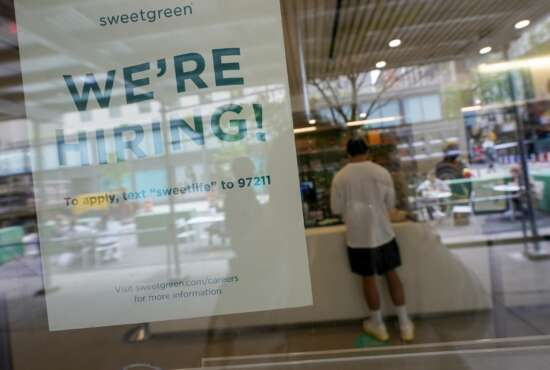 A signs announcing they are hiring hangs in the window of a restaurant in the Greenwich Village neighborhood of Manhattan in New York, Tuesday, May 4, 2021. Some restaurants in New York City are starting to hire employees now that they can increase their indoor dining to 75% of capacity starting May 7. (AP Photo/Mary Altaffer)