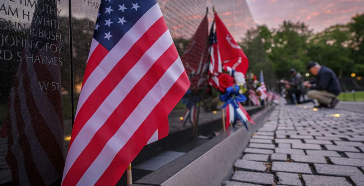 Visitors pause to look for names on the wall at the Vietnam Veterans War Memorial early in the morning on Memorial Day in Washington, Monday, May 31, 2021. (AP Photo/J. David Ake)