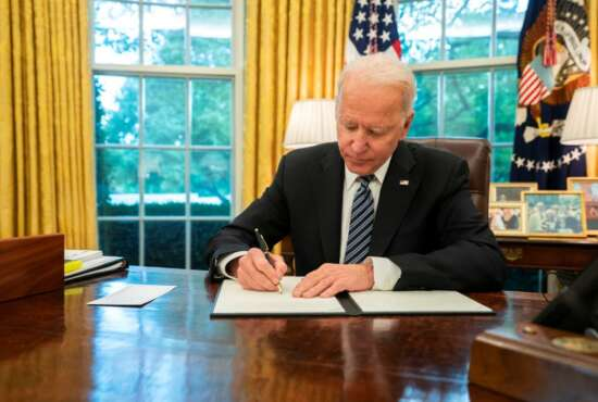 President Joe Biden signs the cybersecurity executive order on May 12.