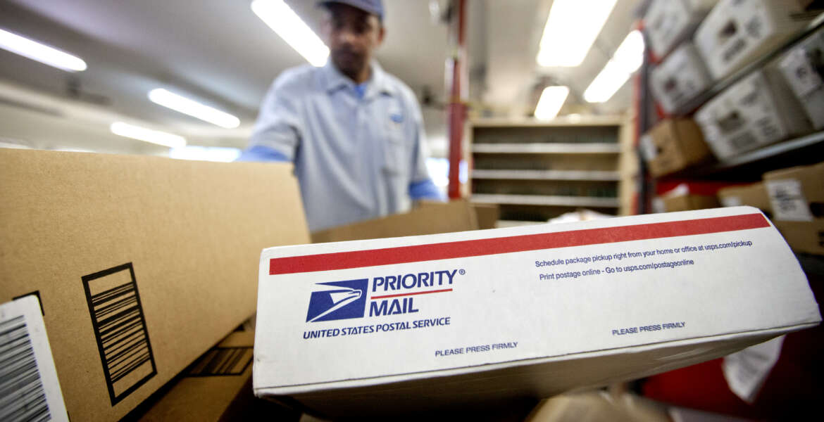 FILE - In this Thursday, Feb. 7, 2013, file photo, packages wait to be sorted in a Post Office as U.S. Postal Service letter carrier  Michael McDonald, gathers mail to load into his truck before making his delivery run, in Atlanta.  The financially struggling U.S. Postal Service said Wednesday, Aug. 14, 2013 it is revamping its priority mail program as part of its efforts to raise revenue and drive new growth in its package delivery business. (AP Photo/David Goldman, File)