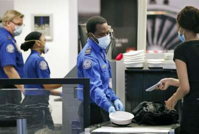 FILE - In this May 18, 2020, file photo, Transportation Security Administration officers wear protective masks at a security screening area at Seattle-Tacoma International Airport in SeaTac, Wash. The Biden administration says it is moving to increase the pay and union rights for security screeners at the nation's airports. The Department of Homeland Security directed the acting head of the TSA to come up with a plan within 90 days to raise the pay of the screeners and expand their rights to collective bargaining.  (AP Photo/Elaine Thompson, File)