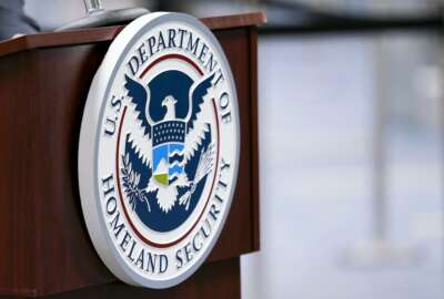 """FILE - In this Nov. 20, 2020, file photo a U.S. Department of Homeland Security plaque is displayed a podium as international passengers arrive at Miami international Airport where they are screened by U.S. Customs and Border Protection in Miami. The damned-if-you-pay-damned-if-you-don't dilemma on ransomware payments has left U.S. officials fumbling about how to respond. While the Biden administration """"strongly discourages"""" paying, it recognizes that failing to pay would be suicidal for some victims. (AP Photo/Lynne Sladky, File)"""