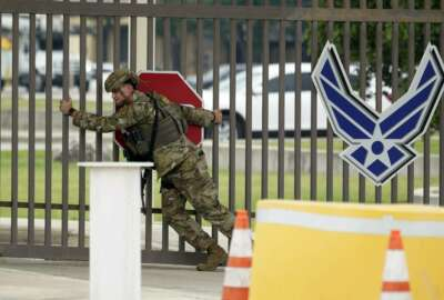 A military policeman closes a gate at JBSA-Lackland Air Force Base gate, Wednesday, June 9, 2021, in San Antonio. The Air Force was put on lockdown as police and military officials say they searched for two people suspected of shooting into the base from outside. (AP Photo/Eric Gay)